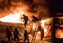 Huge Fire Blazing In Commercial Building And Firefighter On A Roof In Winter Condition.