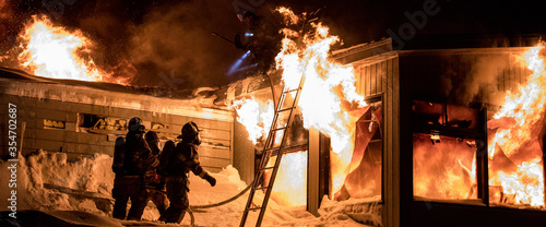 Huge fire blazing in commercial building and firefighter on a roof in winter condition Wallpaper Mural
