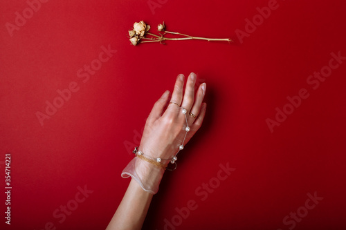 Obraz Fashion art hand woman in the glove with Jewelry in summer time and flowers behind her hand with bright contrasting makeup. Creative beauty photo hand skincare - fototapety do salonu