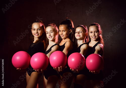 Photo Team of young smiling girls gymnasts in black sport body posing with pink gymnas