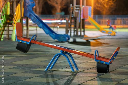 Fototapeta Seesaw swing in preschool yard with soft rubber flooring at night. obraz