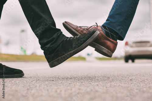Photo close up. two young men greeting each other on a city street.
