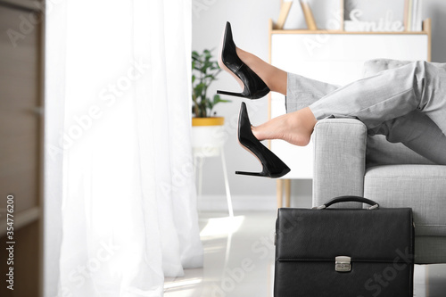 Businesswoman relaxing on sofa after work at home Canvas Print