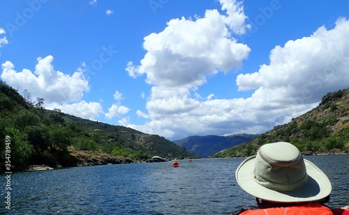 kayaker in orange vest with hat in kayak on river with hills Canvas Print