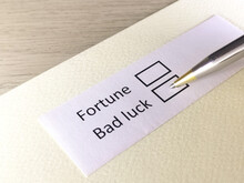 One Person Is Answering Question On A Piece Of Paper. The Person Is Thinking To Be Fortune Or Bad Luck.