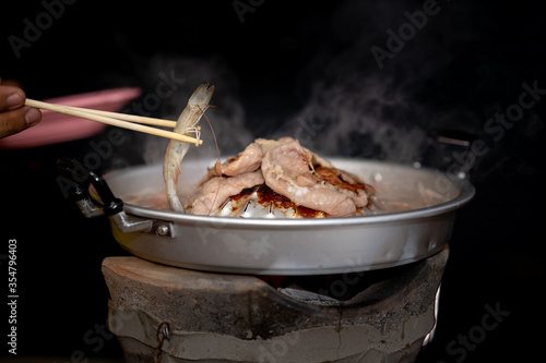 Fototapeta Grilled pork meat and seafood in chopsticks on hot steam smoke water from hot pan for cooking in party, roasted meat on night background for people eating to tasty and delicious food in restaurant obraz