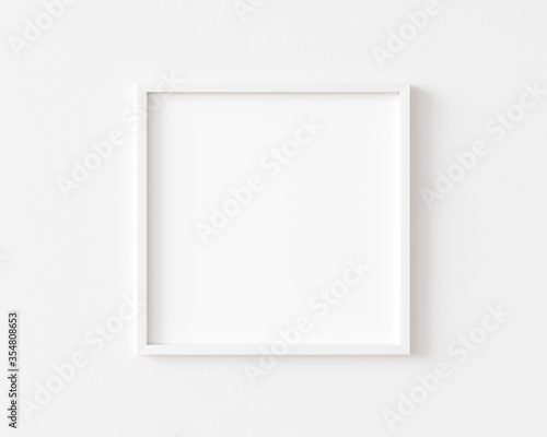 White square photo frame on white wall. 3d illustration.