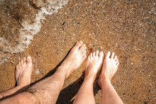 Male And Female Legs Stand On A Sandy Beach. Walking Near The Surf Line. Summer And Beach Concept