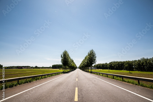 Fototapeta Picturesque country road and clear sky obraz