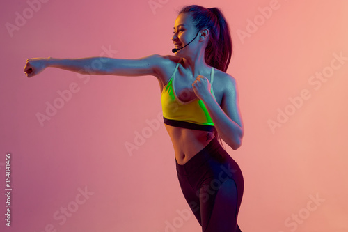 Cute girl fitness instructor teaches Boxing or body combat online training remotely on a bright neon background Wallpaper Mural