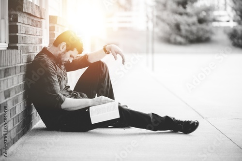 Fotografie, Obraz Young male sitting on the ground and holding the bible in his hands