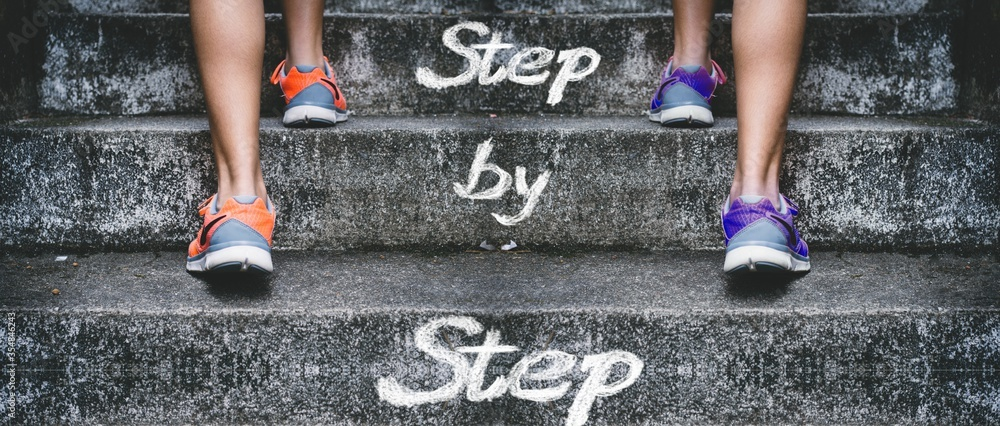 Fototapeta People climbing the stairs with [Step by Step] written on them - concept of success