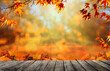 Wooden table with orange fall  leaves, autumn natural background