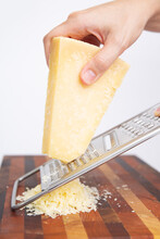 Woman Holding Metal Grater And Grating Cheese On Wooden Board. Isolated On White Background. Studio Shot. Selective Focus. Side View. Dairy Food And Cooking At Home Concept For Flyers And Banners