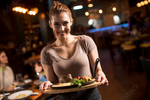 Fotografie, Obraz Waiter woman serving group of friends with food in the restaurant