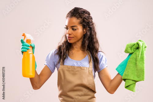 Fototapeta Portrait of african-american housewife who doesn't like cleaning.