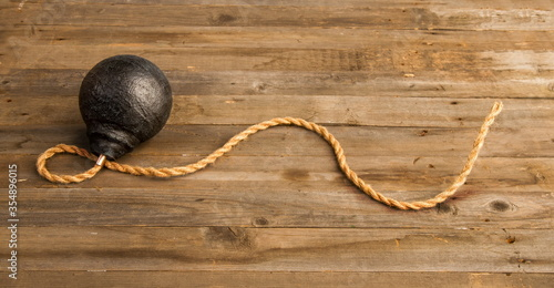 classic round black antique bomb with a long non-burning rope wick on a rough wo Wallpaper Mural