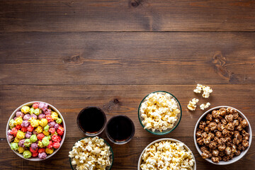 Popcorn and soda - cinema snacks - on wooden table from above space for text