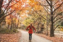 Woman In Country Lane Enjoying The Beautiful Countryside In Autumn