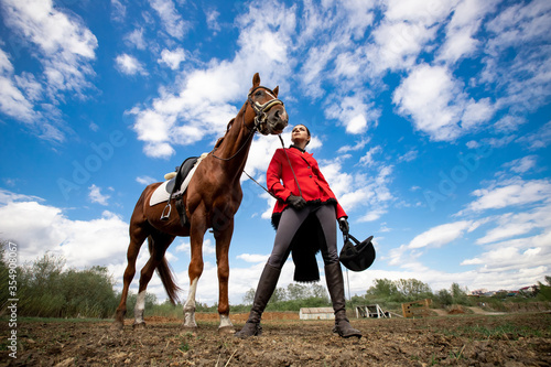 Obraz na plátně Portrait Jockey woman rider with brown horse, concept advertising equestrian clu