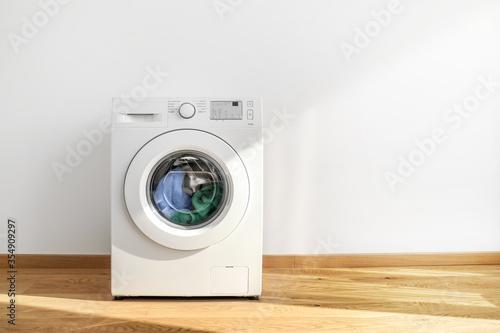 Obraz Working washing machine on white background - fototapety do salonu