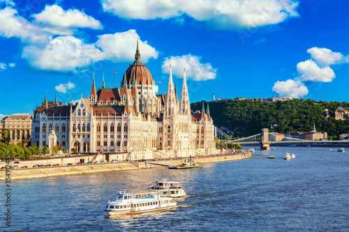 Leinwand Poster Parliament and riverside in Budapest Hungary with sightseeing ships during summer sunny day with blue sky and clouds