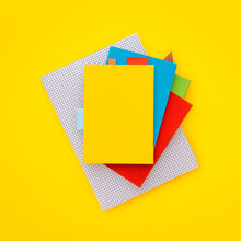 Stack Of Notebooks With Blank Cover On Yellow Table. Top View.