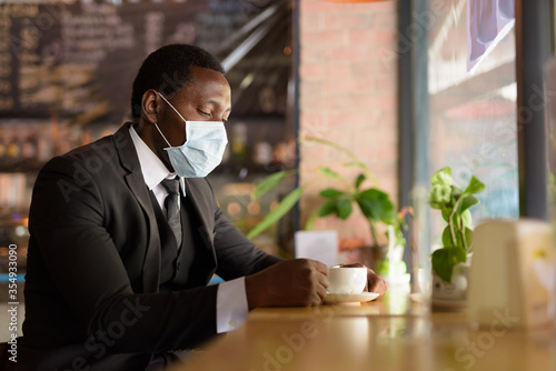 Fototapeta Portrait of African businessman wearing mask while drinking coffee inside the coffee shop as the new normal obraz