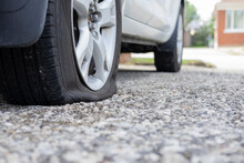 Close Up Of Flat Rear Tire Of White SUV Track Car Vehicle Automobile Punctured By Nail. Summer Day, Residential Street. Selective Focus, Depth Of Field, Space For Copy.