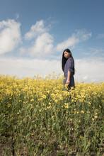 Teenage Girl In Blue Dress Standing In Wild Flower Field