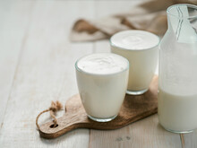 Kefir, Buttermilk Or Yogurt With Probiotics. Yogurt In Glass On White Wooden Background. Probiotic Cold Fermented Dairy Drink. Gut Health, Fermented Products, Healthy Gut Flora Concept. Copy Space