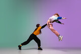 Fototapeta Sport - Beautiful sportive girls dancing hip-hop in stylish clothes on colorful gradient background at dance hall in neon light. Youth culture, movement, style and fashion, action. Fashionable bright portrait