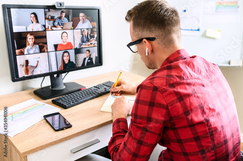 A young busy guy is making notes at the online conference video call with colleagues Wallpaper Mural