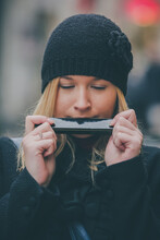 Frontal Portrait Of Young Attractive Blonde Woman Playing Harmonica On The Street. Woman Wearing A Black Hat, Jacket And Playing A Harmonica With Her Mouth With Eyes Closed.