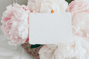 Feminine wedding, birthday mockup scene. Closeup of blank cotton paper card, invitation on pink floral petals. Peony flowers, blossoms. Spring floral, composition. Flat lay, top view.
