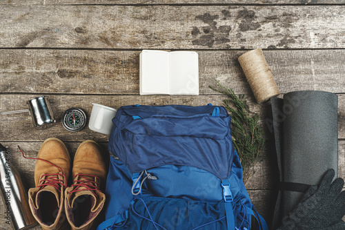 Obraz Backpack and hiking equipment on wooden background, top view - fototapety do salonu