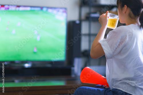 家でスポーツをテレビ観戦する若い女性のイメージ【プロサッカーの動画配信サービス】 Canvas Print