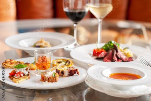 Fotografia レストランのテーブルに並んだ料理とワイン イタリアン