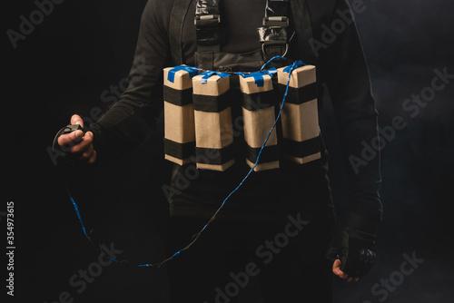 Fotografia Cropped view of terrorist in suicide belt holding detonator isolated on black