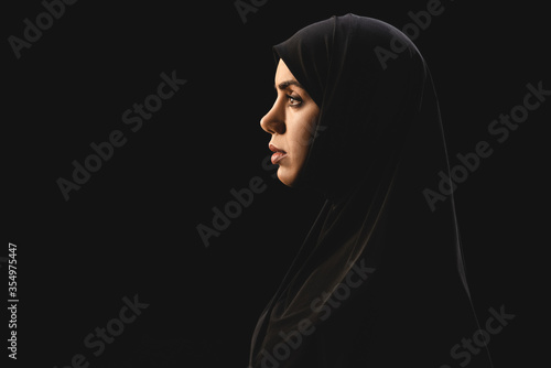 Fotografia Side view of beautiful muslim woman in hijab isolated on black