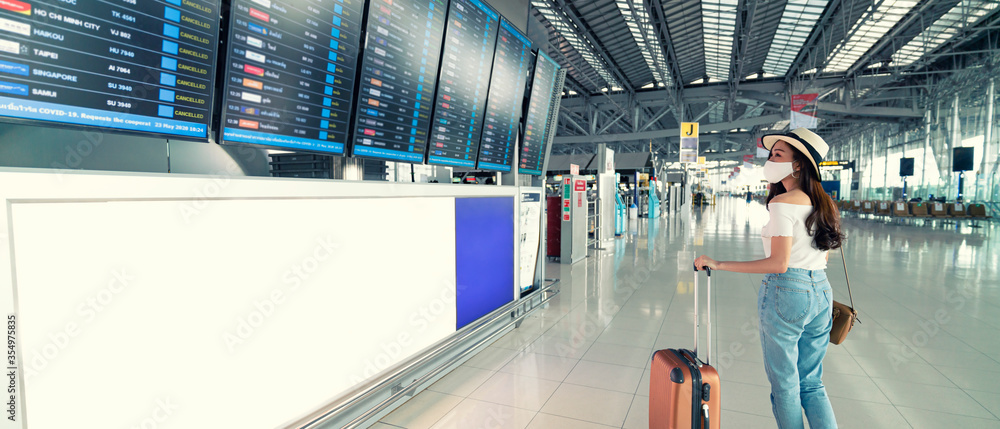 Fototapeta Banner photo of Asian female wearing face mask with suitcase checking flight cancellation status on airport information board in empty airport. airline bankrupt, airline crisis or new normal concept