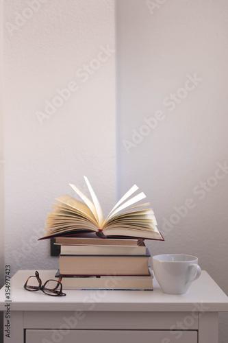 Fotografiet libro abierto sobre varios libros en una mesita de noche blanca, sobre la que ta