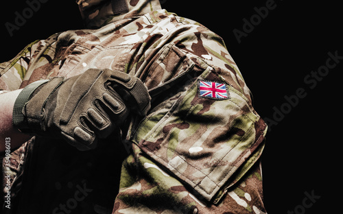British soldier in camouflage shirt and tactical gloves on black background Fototapete