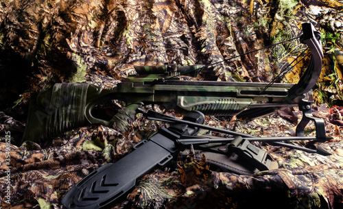 Photo Hunting crossbow with arrows and knife laying on table.