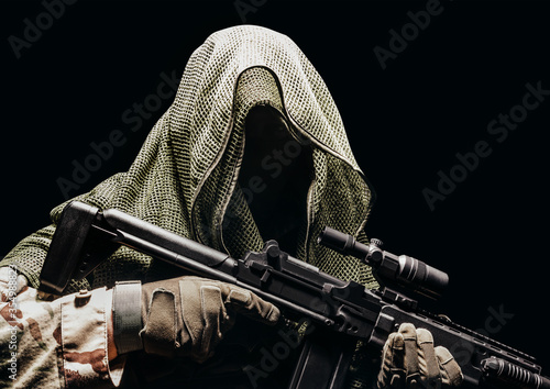 Fototapeta Fully equipped soldier in tactical net scarf with sniper rifle.