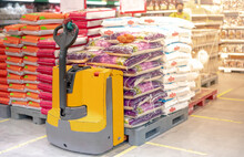 Hand Pallet Truck With The Rice Bag And Plastic Pallets With Goods In The Wholesale Market.