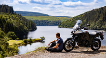 Adventure Motorcycle And Biker Man Traveling, Sitting And Watching Landscape With Lake And Mountains, Freedom Travel Lifestyle In Wales UK