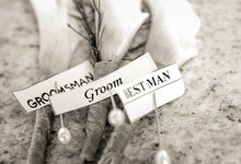 Close Up Black And White Image Of Boutonnieres Of Lilies For Groom, Best Man, And Groomsman With Labels And Stick Pins