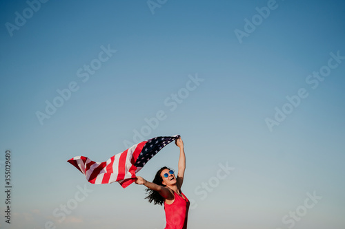 Tela young woman holding United States flag outdoors at sunset