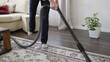 Adult woman cleaning living space indoor with vacuum cleaner